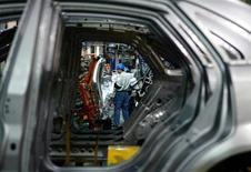 Um trabalhador chinês é enquadrado por carrocerias de Buicks na linha de produção da GM em Xangai. A General Motors disse nesta quarta-feira que irá transferir sua sede de operações internacionais de Xangai para Cingapura no segundo trimestre de 2014. 16 de outubro de 2003. REUTERS/Claro Cortes