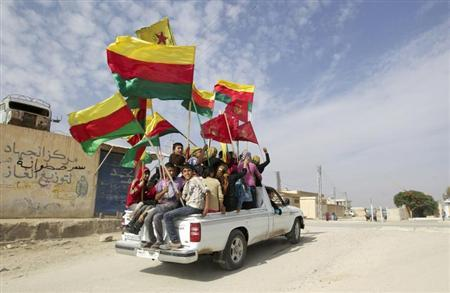 People sit in the back of a truck as they celebrate what they said was the liberation of villages from Islamist rebels near the city of Ras al-Ain in the province of Hasakah, after capturing it from Islamist rebels November 6, 2013. REUTERS/Stringer