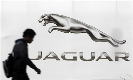 A man walks past a billboard advertising Jaguar in New Delhi February 12, 2013. REUTERS/Mansi Thapliyal
