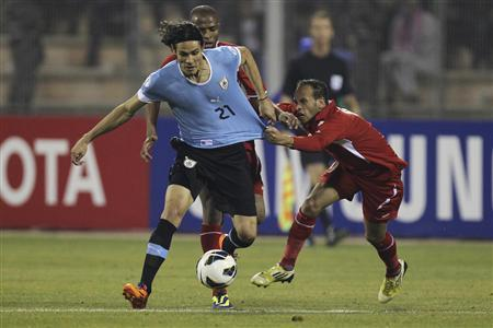 Edinson Cavani of Uruguay (L) fights for the ball with Adnan Adous of Jordan during their World Cup qualifying playoff first leg soccer match at Amman International stadium November 13, 2013. REUTERS/Muhammad Hamed
