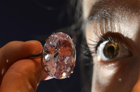 Model Annabeth Murphy-Thomas poses with The Pink Star diamond at Sotheby's auction house in central London in this October 24, 2013 file photo. REUTERS-Toby Melville-Files
