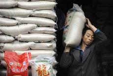 A worker transport packs of rice at a market in Hefei, Anhui province in this November 27, 2009 file photo. REUTERS/Jianan Yu/Files