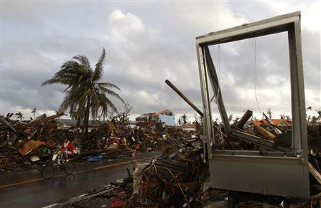 A man rides past a destroyed gasoline pump signboard in the aftermath of super typhoon Haiyan in Tacloban city, central Philippines November 13, 2013. REUTERS/Edgar Su