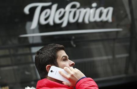 A man talks on a mobile phone as he walks past Spanish telecom group Telefonica's flagship store in central Madrid November 8, 2013. REUTERS/Sergio Perez