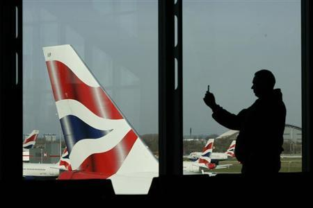 A passenger photographs British Airways aircraft with his mobile telephone at Heathrow Airport near London March 15, 2009. Luke MacGregor/REUTERS