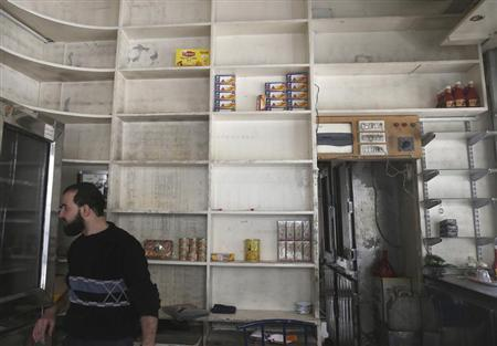 A man is seen inside a half-empty shop due to lack of supplies in the Duma neighbourhood of Damascus November 6, 2013. REUTERS/Bassam Khabieh