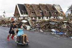 Children play as they pass debris and damaged houses after super typhoon Haiyan battered Tacloban City, in central Philippines November 13, 2013. Philippine officials have been overwhelmed by Haiyan, one of the strongest typhoons on record, which tore through the central Philippines on Friday and flattened Tacloban, coastal capital of Leyte province where officials had feared 10,000 people died, many drowning in a tsunami-like wall of seawater. REUTERS/Edgar Su