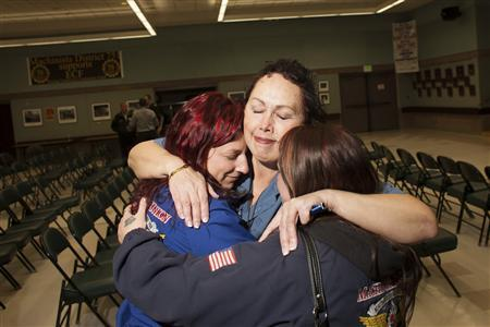 (L - R) Gabrielle Rogano, Hazel Powers, and Rachel Sarzynski embrace after hearing the results of a union vote at the International Association of Machinists District 751 Headquarters in Seattle, Washington November 13, 2013. REUTERS/David Ryder