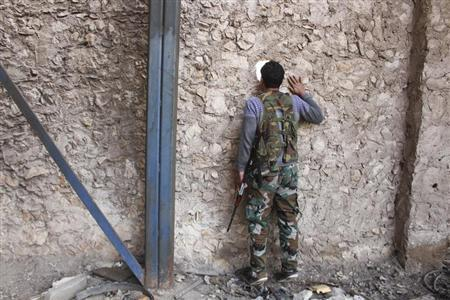 A Fighter from Tawhid Brigade, which operates under the Free Syrian Army, looks through a hole in the wall in Base 80 area of Aleppo, November 10, 2013. REUTERS/Molhem Barakat