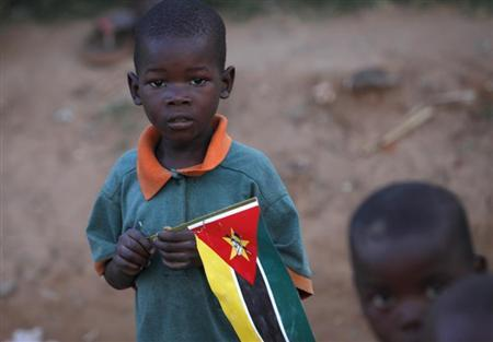 A child clasps a Mozambique flag in a suburb on the outskirt of the capital Maputo in this file picture taken November 2009. REUTERS/Mike Hutchings/Files