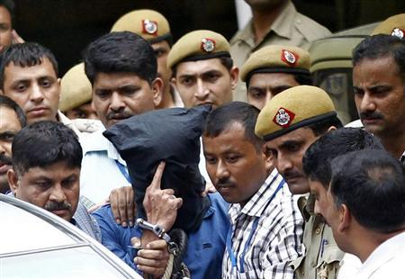 Police escort Yasin Bhatkal (head covered), the key operative of the Indian Mujahideen militant group, outside a court in New Delhi August 30, 2013. REUTERS/Anindito Mukherjee/Files