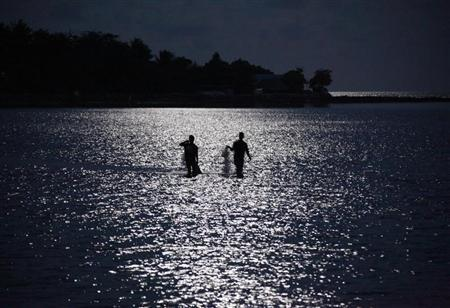 Fishermen are illuminated by the full moon as they prepare to cast their nets near the village of Teaorereke on South Tarawa in the central Pacific island nation of Kiribati May 25, 2013. REUTERS/David Gray