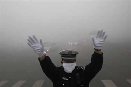 A traffic policeman signals to drivers during a smoggy day in Harbin, Heilongjiang province, October 21, 2013. REUTERS/China Daily