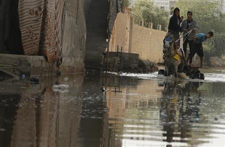 Palestinians ride a horse cart on a street flooded with sewage water from a sewage treatment facility in Gaza City November 14, 2013. REUTERS/Mohammed Salem