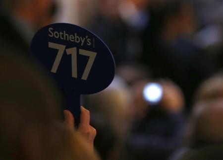 A buyer raises a bid during the sale of jewellery at Sotheby's in Geneva November 13, 2013. REUTERS/Denis Balibouse