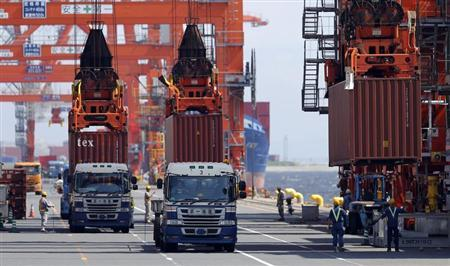 Workers load containers from trucks onto a cargo ship at a port in Tokyo August 19, 2013. REUTERS/Toru Hanai