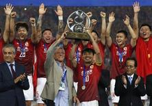 China's Guangzhou Evergrande coach Marcello Lippi (front 2nd L) and player Zheng Zhi (10) hold up the trophy after winning their final match of the AFC Champions' League against South Korea's FC Seoul at Tianhe stadium in the southern Chinese city of Guangzhou November 9, 2013. REUTERS/Bobby Yip