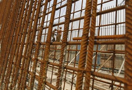 Construction workers fasten iron rods at the construction site of a bridge being built on a highway in Ahmedabad September 30, 2013. REUTERS/Amit Dave/Files