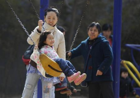 A mother pushes her daughter on a swing in Beijing April 3, 2013. REUTERS/Jason Lee