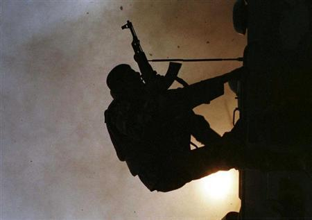 File photo of a Sri Lankan soldier silhouetted against the sun as he jumps off the top of a battle tank in the northwestern town of Madhu March 23, 1999. REUTERS/Anuruddha Lokuhapuarachchi