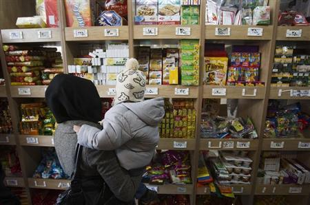 A woman carrying her son stands in front of a food shelf as she shops at a supermarket in northern Tehran, December 12, 2011. REUTERS/Morteza Nikoubazl