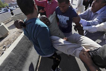 People carry a man who was injured when Libyan militiamen opened fire into a crowd of protesters in Tripoli November 15, 2013. REUTERS/Stringer