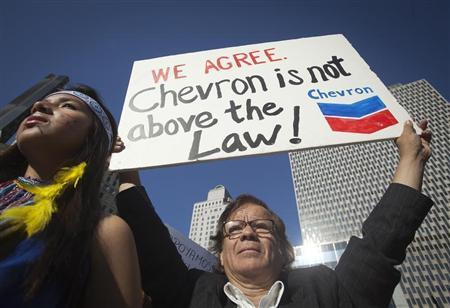 A protester holds up a sign as he demonstrates against Chevron's Racketeer Influenced and Corrupt Organizations (RICO) trial in New York, October 15, 2013. REUTERS/Carlo Allegri