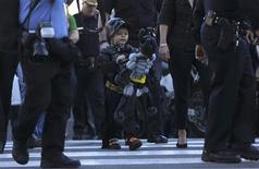 "Five-year-old leukemia survivor Miles Scott, dressed as ""Batkid"" looks at a Batman balloon after a ceremony arranged by the Make- A - Wish Foundation in San Francisco, California November 15, 2013. REUTERS/Stephen Lam"