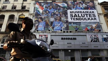 A policeman on a scooter backs out from a parking lot in front of a billboard of cricketer Sachin Tendulkar in Mumbai November 15, 2013. REUTERS/Danish Siddiqui