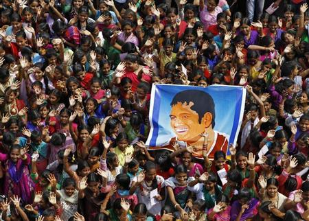 School children wave as they hold a poster of Indian cricketer Sachin Tendulkar at an event to honour him inside a school in the southern Indian city of Chennai November 14, 2013. REUTERS/Babu
