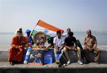A cricket fan dressed as a Hindu holy man, or Sadhu, sits next to portraits of cricketer Sachin Tendulkar outside a stadium in Mumbai November 16, 2013. REUTERS/Danish Siddiqui