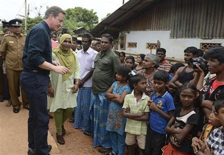Britain's Prime Minister David Cameron talks with Tamil people at the Sabapathi Pillay Welfare Centre in Jaffna, about 400 km (250 miles) north of Colombo November 15, 2013.REUTERS/Stringer