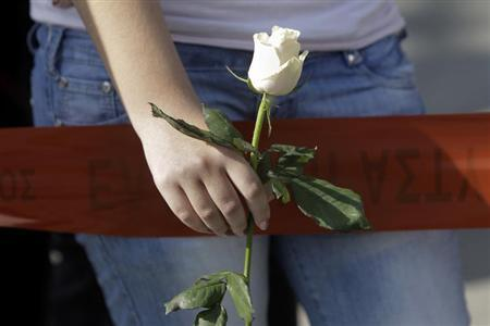 A woman holds a white rose as she stands near the local offices of far-right Golden Dawn party, following last night's shooting, in a northern suburb of Athens November 2, 2013. REUTERS/John Kolesidis