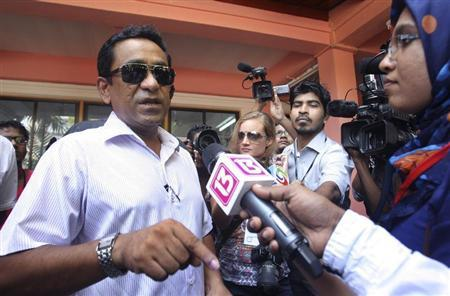Progressive Party of Maldives (PPM) presidential candidate Abdulla Yameen (L) speaks to the media after casting his vote at a polling station during the presidential elections in Male, November 9, 2013. REUTERS/Waheed Mohamed
