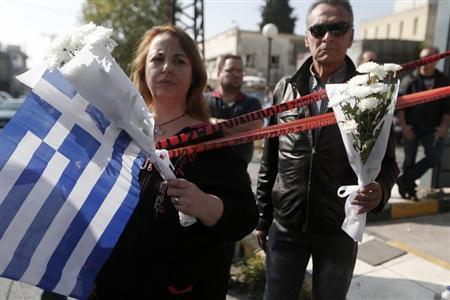 People holding flowers and a Greek flag stand near the local offices of far-right Golden Dawn party, following last night's shooting, in a northern suburb of Athens November 2, 2013. REUTERS/John Kolesidis