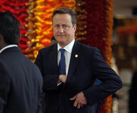 Britain's Prime Minister David Cameron reaches into his pocket as he arrives for the official photograph of Commonwealth heads of states during the Commonwealth Heads of Government Meeting (CHOGM) opening ceremony in Colombo November 15, 2013. REUTERS/Dinuka Liyanawatte