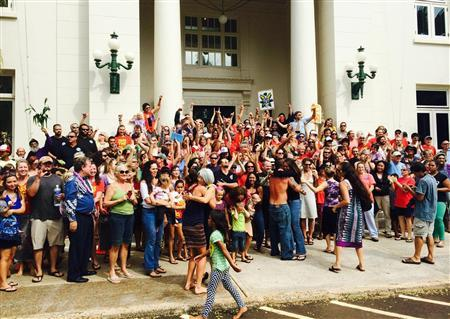 A crowd gathers in celebration on the steps of the historic Kauai County building in Lihue, Hawaii on November 16, 2013 after the Kauai County Council voted 5-2 to override the mayor's recent veto of a bill related to pesticides and genetically modified crops on the island. REUTERS/Christopher D'Angelo