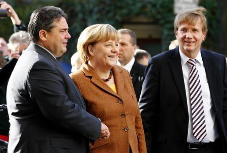 Leader of Germany's Social Democratic Party (SPD) Sigmar Gabriel (L) welcomes German Chancellor and leader of the Christian Democratic Union (CDU) Angela Merkel and Federal Chancellery Minister Ronald Pofalla (R) at the SPD headquarters before coalition talks between Germany's conservative (CDU/CSU) parties and the SPD in Berlin October 30, 2013. REUTERS/Tobias Schwarz