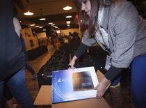 A Sony employee takes a Playstation 4 out of the box in advance of a special sale event put on by Sony at the Standard Hotel in New York November 14, 2013. REUTERS/Carlo Allegri