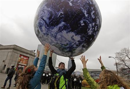 Environmental activists play with a giant globe on the streets in a rally demanding more action to battle climate change during the 19th conference of the United Nations Framework Convention on Climate Change (COP19) in Warsaw November 16, 2013. (Credit: Reuters/Kacper Pempel) Click to enlarge.