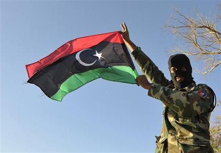 A member of the Libyan army's Thunderbolt Brigade flies the Libyan flag as the army prepares for deployment in Benghazi, November 8, 2013. REUTERS/Esam Omran Al-Fetori