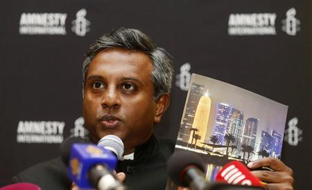 Amnesty International Secretary General Salil Shetty holds up a report titled ''The Dark Side of Migration: Spotlight on Qatar's construction sector ahead of the World Cup'', during a news conference in Doha November 17, 2013. REUTERS/Mohammed Dabbous