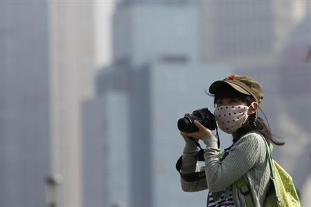 A tourist wears a mask while taking pictures on the Bund in Shanghai during a hazy day November 8, 2013. Chinese cities should close schools, cut working hours and stop outdoor activities during the most severe spells of air pollution, the Ministry of Environmental Protection said on Wednesday. REUTERS/Aly Song