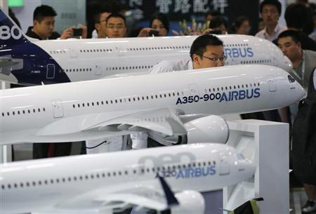 A visitor looks at a miniature Airbus A350-900 passenger aircraft at Aviation Expo China 2013 in Beijing September 25, 2013. REUTERS/Kim Kyung-Hoon