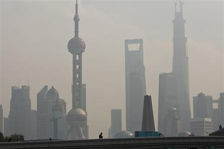 People walk past a bridge in front of the financial district of Pudong in Shanghai during a hazy day November 8, 2013. REUTERS/Aly Song