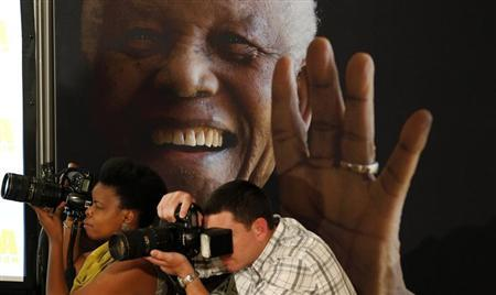 Photographers take pictures in front of a poster of anti-apartheid leader and former president Nelson Mandela during a news conference with the cast of the biographical film ''Mandela: Long Walk to Freedom'' at the Nelson Mandela Centre of Memory in Johannesburg, November 2, 2013. REUTERS/Siphiwe Sibeko