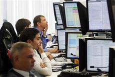 Трейдеры в торговом зале Тройки Диалог в Москве 26 сентября 2011 года. Рубль дорожает на биржевой сессии понедельника, приблизившись к безынтервенционной области Центробанка, отражая позитивную динамику валют-аналогов и евро к доллару США, а также в преддверии крупных налогов конца месяца, которые могут спровоцировать экспортеров на рост продаж валютной выручки. REUTERS/Denis Sinyakov
