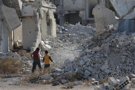 Children walk past damage that was caused by shelling from forces loyal to President Bashar al-Assad, activists said, along a street in Duma neighbourhood in Damascus November 17, 2013. REUTERS/Bassam Khabieh