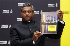 "Amnesty International Secretary General Salil Shetty holds up a report titled ""The Dark Side of Migration: Spotlight on Qatar's construction sector ahead of the World Cup"", during a news conference in Doha November 17, 2013. REUTERS/Mohammed Dabbous"