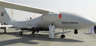 Un visitante habla por teléfono bajo la sombra de una drone en la Feria Aérea de Dubái. Airbus y Boeing firmaron el lunes acuerdos para comprarle a Abu Dhabi cerca de 5.000 millones de dólares en partes y materiales, en negociaciones que los estados del Golfo Pérsico esperan den un impulso recíproco a sus economías tras las enormes órdenes de compra realizadas a los fabricantes de aeronaves un día antes. REUTERS/Caren Firouz